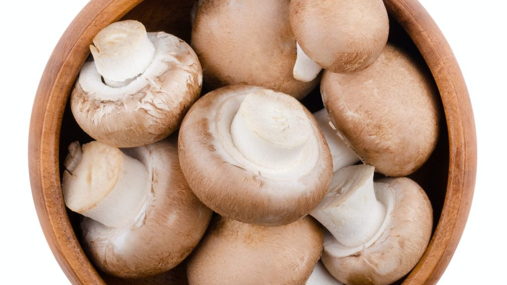 Brown champignons in a bowl over white