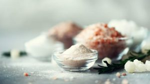 Mix of different salt types on grey concrete background. Sea salts, black and pink Himalayan salt